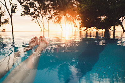 Legs of woman in infinity pool at sunset, Nai Thon Beach, Phuket, Thailand - p300m2166403 by Christophe Papke