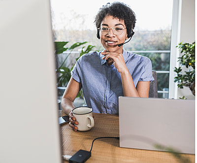 Woman sitting in front of computer, having video conference - p300m2244085 by Uwe Umstätter