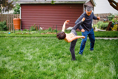 A shirtless tween boy roughhouses with father in the yard in spring - p1166m2157366 by Cavan Images