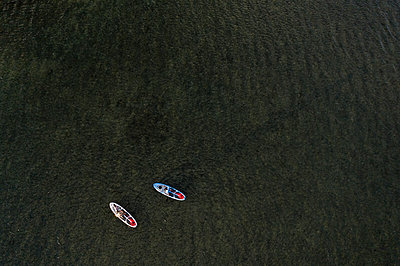 Two people using stand up paddleboards in the ocean in Hawai'i - p1166m2279551 by Cavan Images