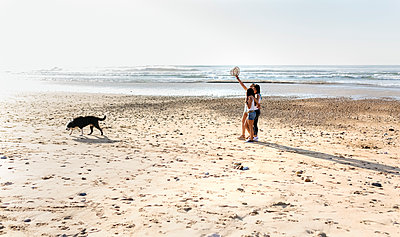 Three women with dog walking on the beach - p300m2114716 by Marco Govel