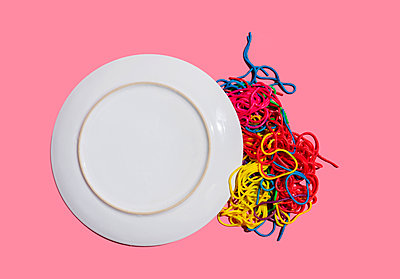 Studio shot of colorful pasta spilling from dropped plate - p300m2198269 by Gemma Ferrando