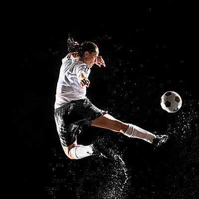 Hispanic soccer player splashing in water - p555m1454261 by Erik Isakson