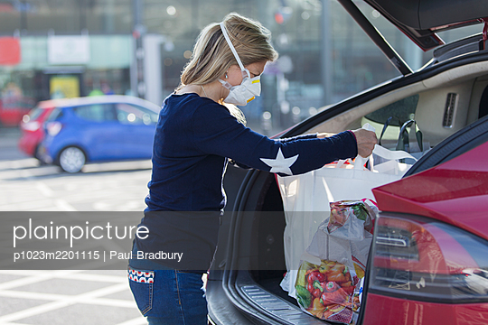 Woman in face mask loading groceries into car in parking lot - p1023m2201115 by Paul Bradbury