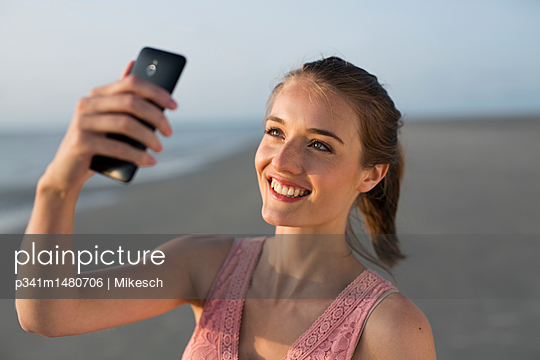 Young woman on beach takes a selfie - p341m1480706 by Mikesch