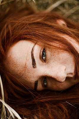 Close-up portrait of teenage girl with red head lying on grassy - p1166m2113137 by Cavan Images