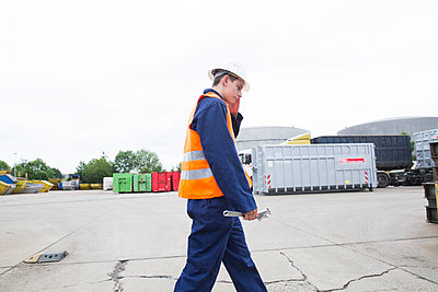 worker young male with helmet outside walking - p1166m2147607 by Cavan Images