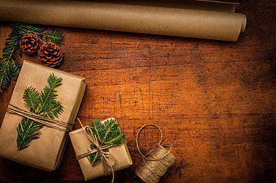 Pine fronds tied to Christmas presents - p1427m2163692 by Tetra Images
