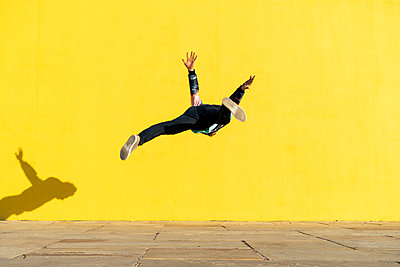 Acrobat jumping somersaults in front of yellow wall - p300m2012266 by VITTA GALLERY