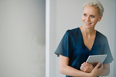 Smiling female entrepreneur with digital tablet looking away while standing against wall in office - p300m2214167 by Kniel Synnatzschke