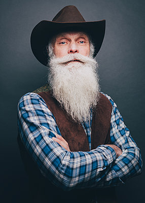 Bearded senior man wearing cowboy hat standing arms crossed against gray background - p426m1588487 by Maskot