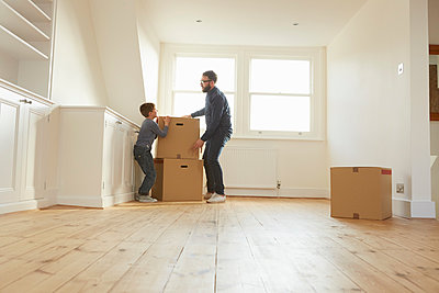 Mid adult man and son stacking cardboard box in new home - p429m1407991 by Emma Kim