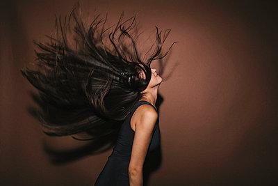 Junge Frau schüttelt ihre langen dunklen Haare - p586m953772 von Kniel Synnatzschke