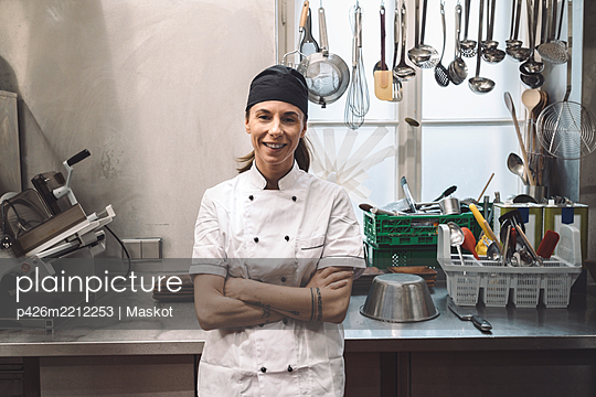 Portrait of smiling female chef with arms crossed in commercial kitchen - p426m2212253 by Maskot
