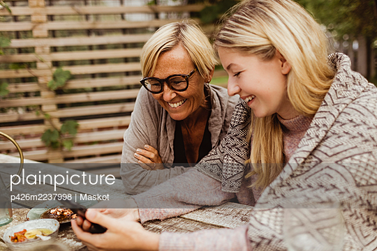 Smiling granddaughter using smart phone sitting with grandmother in front yard - p426m2237998 by Maskot