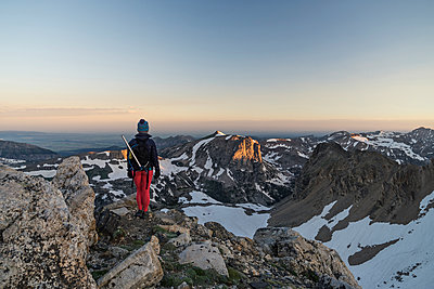 Rear view of hiker standing on mountain against sky during sunset - p1166m1545810 by Cavan Social