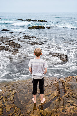 Rear view of boy looking at sea while standing on rocks against clear sky - p1166m2025286 by Cavan Images