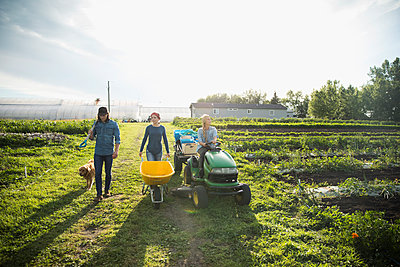 Farmers with wheelbarrow and tractor on sunny farm - p1192m1493129 by Hero Images