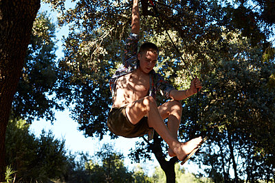 France, teenage boy on a swing at tree - p300m2083153 by Antje Merkel