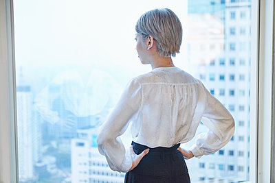 Rear view of businesswoman, hands on hips, looking out of window - p429m1514109 by Philippe Roy