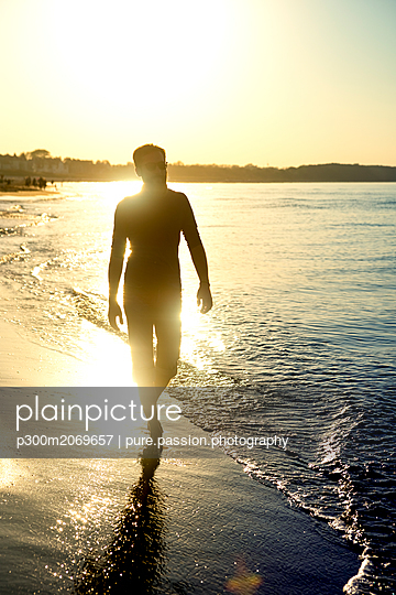 Silhouette of man, walking at the beach at sunset - p300m2069657 by pure.passion.photography