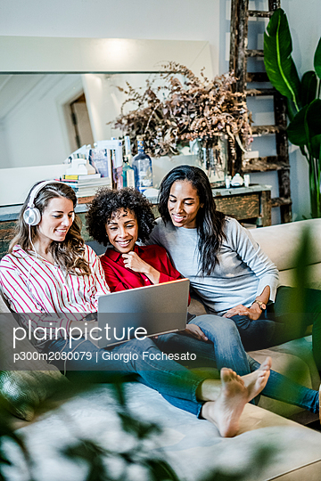 Three happy women with laptop sitting on couch - p300m2080079 by Giorgio Fochesato