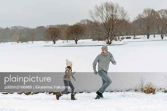 Father and daughter running in winter landscape - p300m2166889 by Ekaterina Yakunina