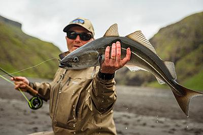 Man holding caught fish - p312m2139492 by Hans Berggren