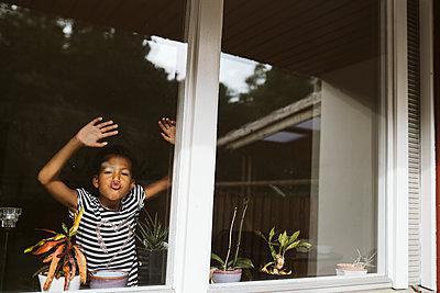 Girl looking through window - p312m2162189 by Stina Gränfors
