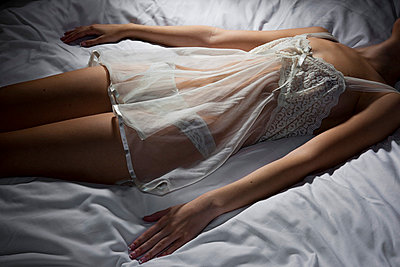 Woman lying on a bed in lingerie - p4130728 by Tuomas Marttila