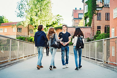 Male teenager walking with friends on bridge - p426m1085583f by Maskot
