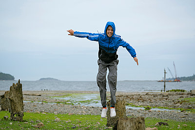 Teenage boy jumping from tree stump, Pacific Rim National Park, Vancouver Island, Canada - p924m1422745 by Raphye Alexius