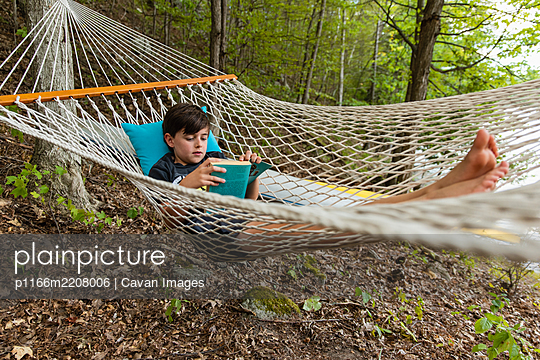 Young boy laying in a woven hammock relaxing and reading a book. - p1166m2208006 by Cavan Images