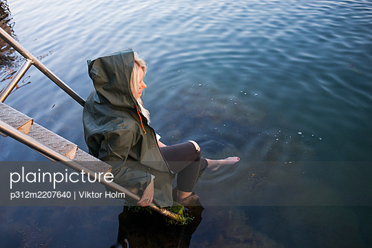 Woman with feet in sea - p312m2207640 by Viktor Holm