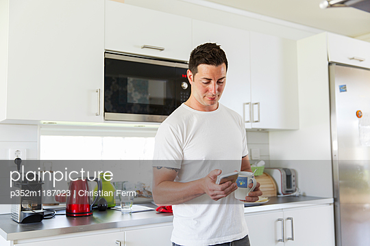 Sweden, Man using mobile phone in kitchen