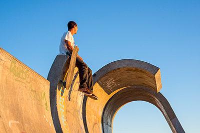 Skateboarder sitting on top of ramp - p1201m1050386 by Paul Abbitt