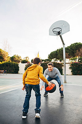 Father and son playing basketball on an outdoor court - p300m1562319 by Bonninstudio