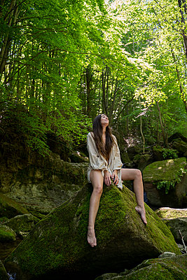 Young woman sitting on a rock in the forest, Garrotxa, Spain - p300m2113812 by VITTA GALLERY