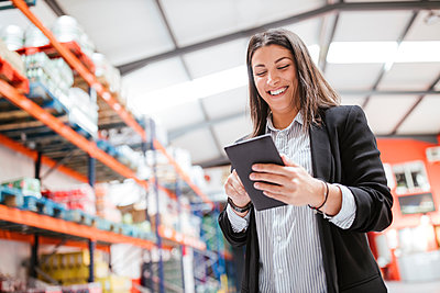 Smiling female manager using digital tablet in illuminated distribution warehouse - p300m2267032 by DREAMSTOCK1982