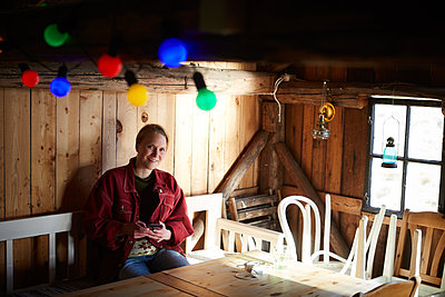 Portrait of smiling young woman using smart phone while sitting at table in log cabin - p426m2117205 by Maskot