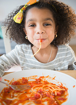 African American girl eating spaghetti at table - p555m1415563 by JGI/Jamie Grill