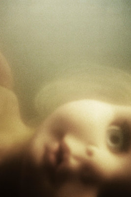 Close up dolls face underwater - p597m1016198 by Tim Robinson