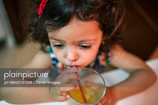 Adorable little girl drinking an orange juice - p1166m2131248 by Cavan Images