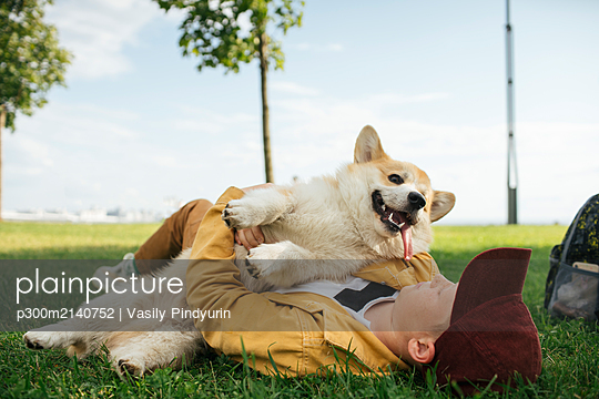 Boy with Welsh Corgi Pembroke in a park - p300m2140752 by Vasily Pindyurin
