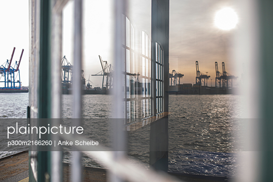 Germany, Hamburg, Ovelgonne, Port on river Elbe reflected in window - p300m2166260 by Anke Scheibe