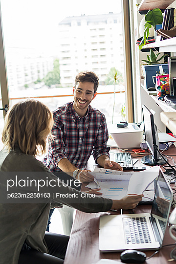Business people reviewing documents in office - p623m2258163 by Frederic Cirou
