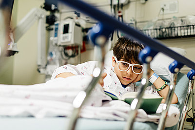 Low angle view of boy wearing eyeglasses reading book while relaxing on bed in hospital - p1166m2067534 by Cavan Images