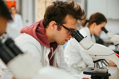 Laboratory technicians using microscopes in lab - p300m1416483 by Zeljko Dangubic