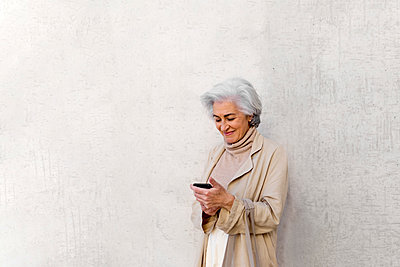 Smiling mature woman using mobile phone in front of wall - p300m2281458 by PICUA ESTUDIO