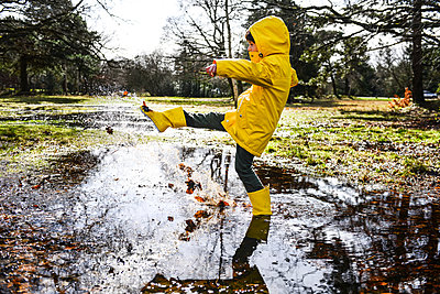 Boy in yellow anorak splashing in park puddle - p429m1407947 by Bonfanti Diego